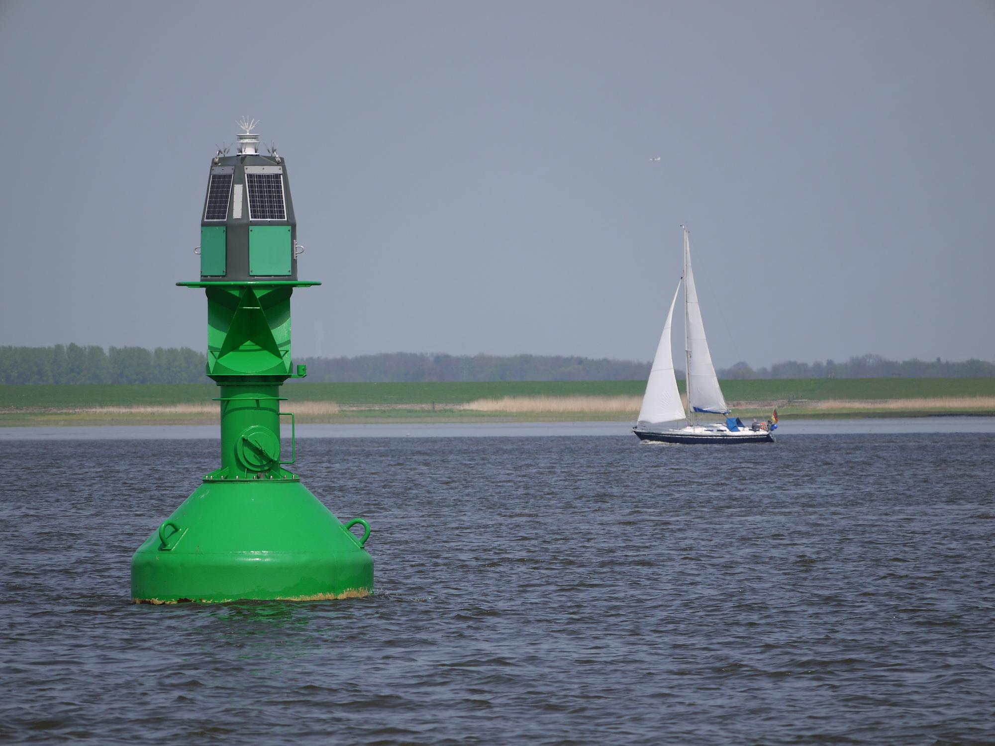 verkehrsregeln schifffahrt boje mit segelboot im hintergrund