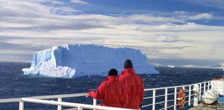 kreuzfahrt ökobilanz paar an der reling eines schiffs mit einem eisberg im hintergrund